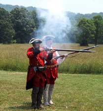 Re-enactors fire colonial rifles at Family Frontier Day at Fort Edwards.